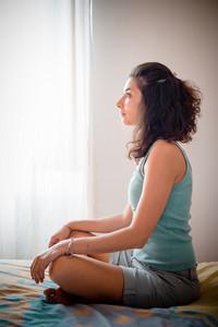 beautiful woman meditating at home
