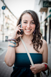 beautiful woman on the phone walking in the city