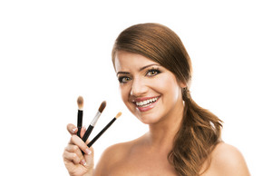 Beautiful woman putting make up on herself and holding make up brushes, isolated on white