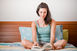 beautiful woman reading in bed at home