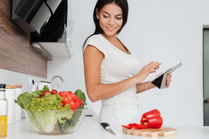 Beautiful woman reading recipe from tablet computer in the kitchen. Looking at products.