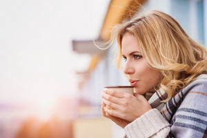 Beautiful woman relaxing at home with cup of  coffee