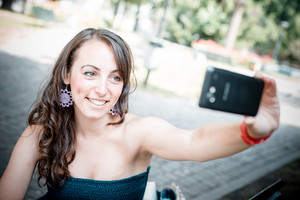 beautiful woman taking self-portrait with smart-phone in the city