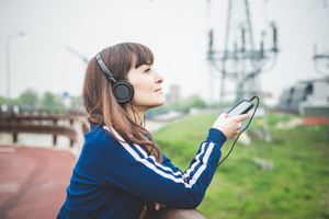 beautiful woman using smart phone and listening music in a desolate lurban landscape