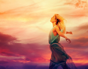 Beautiful woman with arms open wide at sunset