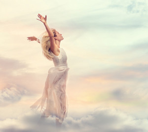 Beautiful woman with arms open wide in the sky
