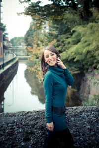 beautiful woman with turtleneck on the phone in the city autumn