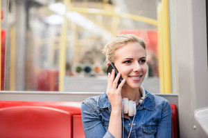 Beautiful young blond woman in denim shirt in subway train, holding a smart phone, making a phone call
