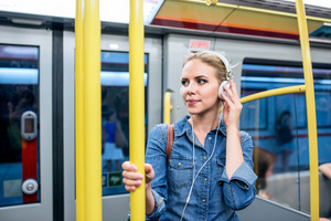 Beautiful young blond woman in denim shirt standing in subway train with white headphones listening music