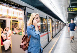 Beautiful young blond woman in denim shirt with smartphone making phone call at the underground platform, getting off a train.