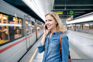 Beautiful young blond woman in denim shirt with smartphone making phone call. Standing at the underground platform, waiting to enter a train.