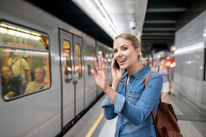 Beautiful young blond woman in denim shirt with smartphone making phone call. Standing at the underground platform, waving to somebody