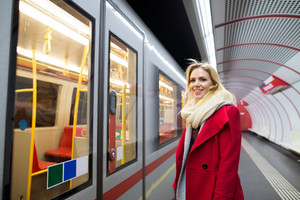 Beautiful young blond woman in red coat at the underground platform, waiting
