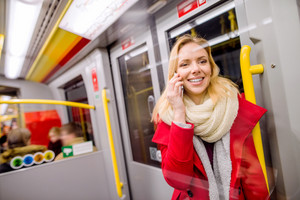Beautiful young blond woman in red coat in subway train, holding a smart phone, making a phone call