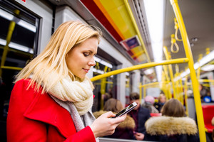 Beautiful young blond woman in red coat in subway train, holding a smart phone, texting
