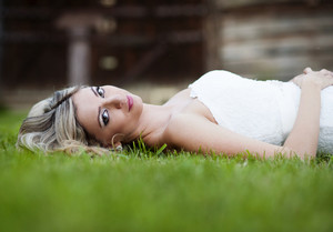 Beautiful young blonde bride lying on the grass