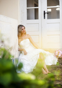 Beautiful young blonde bride posing by old house