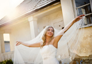 Beautiful young blonde bride with veil posing by old house