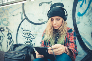 beautiful young blonde hair woman hipster listening music in the city