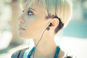 beautiful young blonde short hair hipster woman listening music earphones in the city