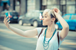 beautiful young blonde short hair hipster woman selfie in the city