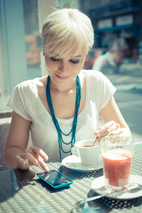 beautiful young blonde short hair hipster woman using smart phone at the cafe
