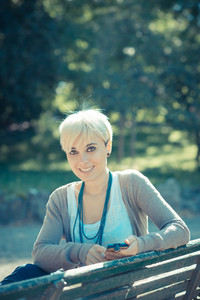 beautiful young blonde short hair hipster woman using smart phone in the city