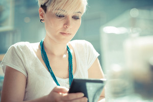beautiful young blonde short hair hipster woman using tablet at the cafe