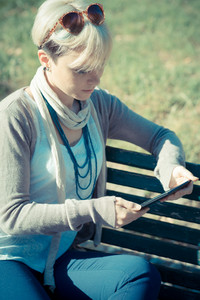 beautiful young blonde short hair hipster woman using tablet in the city
