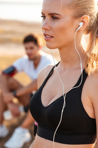Beautiful young blonde sports woman with earphones outdoors