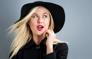 Beautiful young blonde woman in a black coat and hat