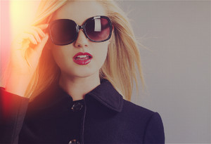 Beautiful young blonde woman in a black coat and sunglasses in led grid concept