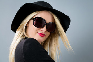 Beautiful young blonde woman in a black coat, hat and sunglasses