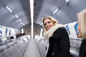 Beautiful young blonde woman in black coat and big woolen scarf standing at the escalator in Vienna subway