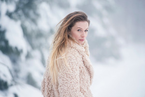 Beautiful young blonde woman in fur coat on a walk in winter nature. Snowy day.