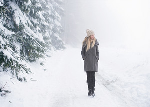 Beautiful young blonde woman in gray coat on a walk in winter nature. Snowy day.