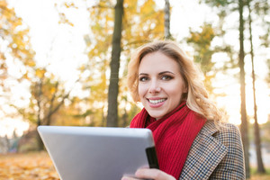 Beautiful young blonde woman in red knitted scarf and checked coat holding tablet, smiling. Sunny autumn park.