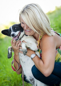Beautiful young blonde woman is hugging and playing with her cute puppy outdoor