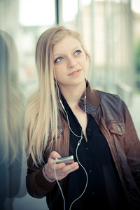 beautiful young blonde woman using smart phone in the city