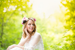 Beautiful young bride in wedding dress with flower wreath sitting outside in green nature.