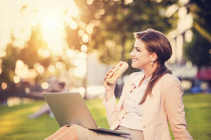 Beautiful young business woman sitting in a park during a lunch break.