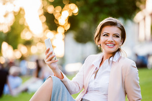 Beautiful young businesswoman sitting in a park during a lunch break, checking her smartphone, sunny summer day.