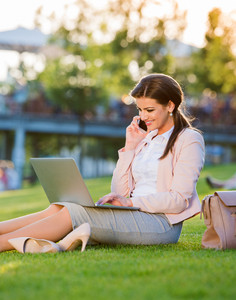 Beautiful young businesswoman sitting in a park on the grass during a lunch break, working on laptop, making a phone call, sunny summer day.