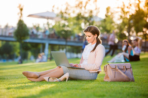 Beautiful young businesswoman sitting in a park on the grass during a lunch break, working on laptop, sunny summer day.