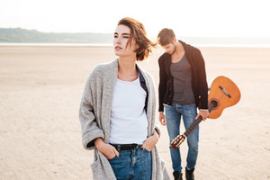 Beautiful young casual couple standing at the seashore with guitar