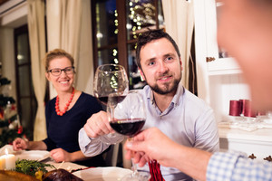 Beautiful young couple celebrating Christmas together with their family, clinking with wine glasses.