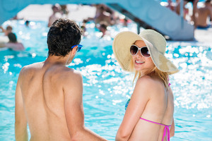 Beautiful young couple having fun outside in the swimming pool