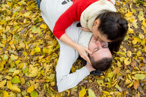 Beautiful young couple in autumn park lying on the ground covered with yellow leaves, kissing