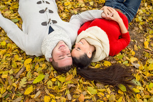 Beautiful young couple in autumn park lying on the ground covered with yellow leaves