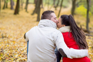 Beautiful young couple in autumn park sitting on the ground covered with yellow leaves, kissing. Back view.
